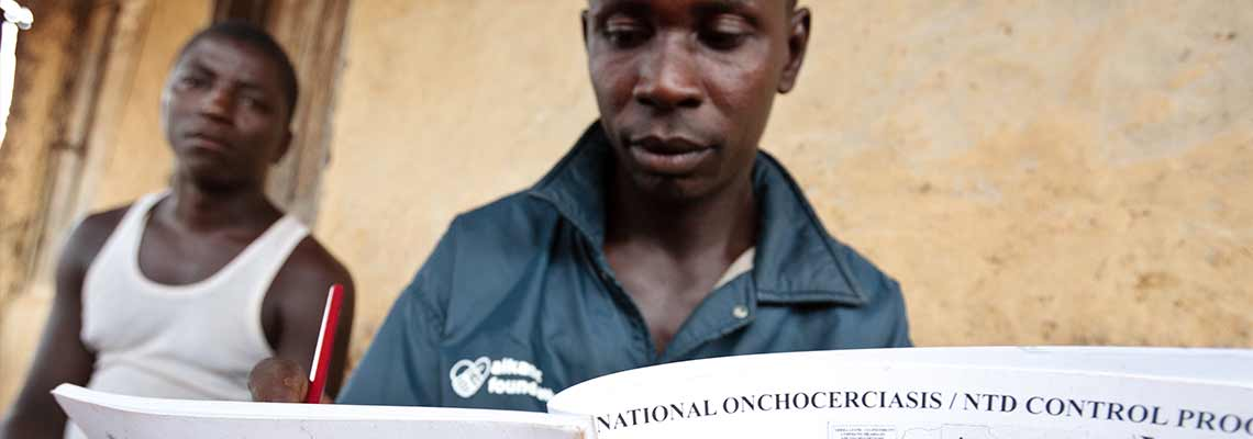 a healthcare worker reads document on Onchocerciasis