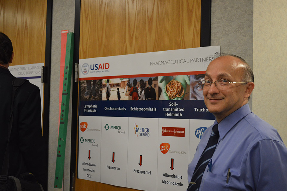 Omar Dary, Ph.D, USAID Nutrition Health Science Specialist, poses next to poster.