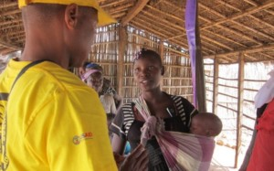 a worker shares information with a woman while holding her baby