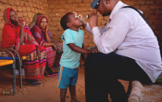 Anwar is examined by a doctor from Sightsavers. Kate Holt, Sightsavers
