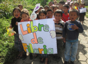 Children march and carry a sign that says Libre de Filaria