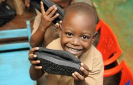 Children show off their new TOMS shoes