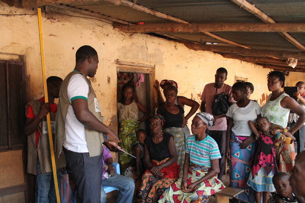 Community health workers talk with Togolese villagers.