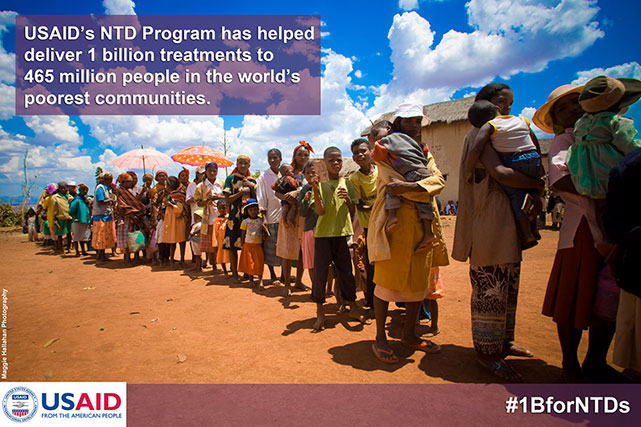 USAID's NTD Program has helped deliver 1 billion treatments to 456 million people in the world's poorest communities. Photo of women and children waiting in a line.