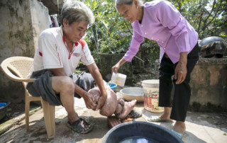 Truong Van Duc washes his leg, which is swollen from lymphedema caused by lymphatic filariasis. Proper self-care is essential for preventing further complications. Photo credit: RTI International/Nguyen Minh Duc